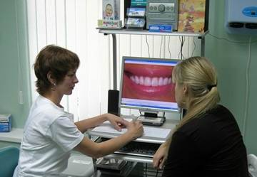 гигиенист стоматологической клиники Диал-Дент объясняет пациенту как правильно пользоваться зубными протезами
